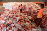 PENYALURAN  BERAS PPKM DI ACEH. Pekerja mengenakan protokol kesehatan mempersiapkan  beras bantuan PPKM  hasil panen petani tahun 2021 saat proses penyaluran di Gudang Perum Bulog Aceh, Desa Siron, Kabupaten Aceh Besar, Aceh, Jumat (23/7/2021). Perum Bulog menyiapkan sebanyak 200.000 ton untuk tambahan bantuan beras PPKM  tahun 2021, sebanyak 4.261 ton di antaranya mulai di salurkan di provinsi Aceh untuk sebanyak 4.267.174 keluarga penerima manfaat (PKM) bekerjasama dengan PT P POS Indonesia . ANTARA FOTO/Ampelsa.