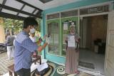 Juru Bayar Kantor Pos Indonesia mendokumentasikan warga penerima Bantuan Sosial Tunai (BST) Kemensos di desa Tegalurung, Balongan, Indramayu, Jawa Barat, Jumat (23/7/2021). Kementerian Sosial melalui PT Pos Indonesia (Persero) menyalurkan Bantuan Sosial Tunai (BST) untuk periode Mei-Juni 2021 sebesar Rp600 ribu secara jemput bola atau di kirim ke rumah Keluarga Penerima Manfaat (KPM). ANTARA FOTO/Dedhez Anggara/agr