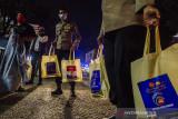 Anggota Kepolisian membawa bantuan sosial sembako untuk diberikan kepada seorang pemulung di Bandung, Jawa Barat, Jumat (23/7/2021) malam. Sedikitnya 500 paket bansos sembako diberikan oleh aparat gabungan TNI-Polri kepada warga, pemulung, pedagang kaki lima dan pengemudi ojek daring sebagai bentuk kepedulian terhadap masyarakat yang terdampak masa PPKM pandemi COVID-19 khususnya sektor perekomian. ANTARA FOTO/Novrian Arbi/agr