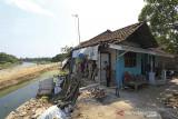 Warga melihat kondisi rumah yang rusak akibat longsor di Desa Kertasmaya, Indramayu, Jawa Barat, Sabtu (24/7/2021). Pergerakan tanah yang terjadi di bantaran Sungai Cimanuk tersebut telah menyebabkan tiga rumah warga rusak dan penghuninya terpaksa mengungsi. ANTARA FOTO/Dedhez Anggara/agr