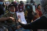 Petugas melayani warga penerima Bantuan Sosial Tunai (BST) di Surabaya, Jawa Timur, Minggu (25/7/2021). Kantor Pos Surabaya menyalurkan BST program pemerintah tersebut kepada 172. 870 Keluarga Penerima Manfaat (KPM) di Surabaya yang dilakukan secara bertahap. Antara Jatim/Didik Suhartono/zk