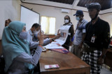 Petugas memotret Pecalang atau petugas keamanan adat Bali yang menerima Bantuan Sosial Tunai (BST) saat pembayaran BST di kawasan Sanur, Denpasar, Bali, Senin (26/7/2021). Bantuan Sosial Tunai tahap lima dan enam sebesar total Rp600 ribu untuk dua bulan tersebut mulai disalurkan kepada 9.569 Keluarga Penerima Manfaat (KPM) di wilayah Denpasar untuk membantu perekonomian masyarakat yang terdampak pandemi COVID-19. ANTARA FOTO/Fikri Yusuf/nym.