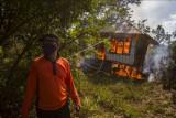 Warga berdiri di dekat pondok yang terbakar akibat kebakaran lahan di kawasan Landasan Ulin Timur, Banjarbaru, Kalimantan Selatan, Senin (26/7/2021). Kebakaran hutan dan lahan (Karhutla) mulai terjadi di sejumlah wilayah Kalimantan Selatan yang mendekati permukiman penduduk. ANTARA FOTO/Bayu Pratama S/nym.