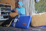 Ria Trans Suci (35) menyelesaikan pembuatan tas rajut berbahan dasar tali kur di Kewijenan Santren, Kelurahan Jelak Ombo, Kabupaten Jombang, Jawa Timur, Senin (26/7/2021). Kerajinan tangan ini tetap bertahan di tengah pandemi dengan mengandalkan pesanan dari para pembeli dan dipasarkan melalui media sosial dengan harga mulai Rp 100 ribu-Rp 500 ribu per buah. Antara Jatim/Syaiful Arif/zk