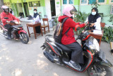 Guru meminjamkan buku kepada wali murid secara lantatur di halaman Madrasah Ibtidaiyah Negeri 2 Kediri, Jawa Timur, Senin (26/7/2021). Layanan peminjaman buku secara lantatur tersebut guna menunjang pembelajaran daring seiring Pemberlakuan Pembatasan Kegiatan Masyarakat (PPKM). Antara Jatim/Prasetia Fauzani/zk