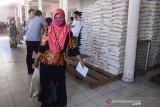 PENYALURAN BERAS PKH DI KANTOR POS BANDA ACEH. Warga membawa sekarung beras seusai penyaluran di Kantor PT POS Indonesia, Banda Aceh, Aceh, Senin (26/7/2021). Pada masa Pemberlakuan Pembatasan Kegiatan Masyarakat (PPKM), pemerintah menyalurkan Bantuan Sosial Tunai (BST) dan Program Keluarga Harapan (PKH) kepada masing masing 10 juta penerima plus sebanyak 10 kilogram beras. ANTARA FOTO/Ampelsa