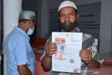 PENYALURAN BST DI KANTOR POS BANDA ACEH. Warga memperlihatkan Bantuan Sosial Tunai (BST) saat penyaluran di Kantor PT POS Indonesia, Banda Aceh, Aceh, Senin (26/7/2021). Pada masa Pemberlakuan Pembatasan Kegiatan Masyarakat (PPKM), pemerintah menyalurkan Bantuan Sosial Tunai (BST) dan Program Keluarga Harapan (PKH) kepada masing masing 10 juta penerima plus sebanyak 10 kilogram beras. ANTARA FOTO/Ampelsa