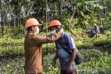 Administratur KPH Ciamis Sukidi (kiri) membantu memakaikan masker kepada seorang mitra kerja Perhutani di RPH Gadung BPKH Banjar Utara, Kabupaten Ciamis, Jawa Barat, Senin (26/7/2021). Perhutani KPH Ciamis membagikan vitamin, sembako dan masker kepada 579 orang mitra kerja Perhutani di kawasan hutan sebagai bentuk kepedulian terhadap para pekerja selama pandemi COVID-19. ANTARA FOTO/Adeng Bustomi/agr
