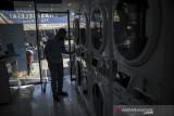 Pekerja mengoperasikan mesin cuci di sebuah jasa laundry di Jalan Dipatiukur, Bandung, Jawa Barat, Senin (26/7/2021). Pada perpanjangan PPKM level 4 hingga 2 Agustus mendatang, pemerintah pusat mengijinkan PKL, toko kelontong, pangkas rambut, laundry, rumah makan, pedagang asongan, dan bengkel kecil untuk beroperasi dengan protokol kesehatan ketat hingga pukul 20.00. ANTARA FOTO/Raisan Al Farisi/agr