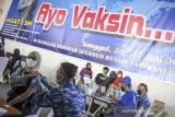 Tenaga kesehatan menyuntikkan vaksin COVID-19 kepada warga di Hanggar Lapangan Udara Husein Sastranegara, Bandung, Jawa Barat, Senin (26/7/2021). Menjelang peringatan Hari Bakti TNI AU ke-74, TNI AU Badan Koordinasi Daerah (Bakorda) Bandung memberikan 4.000 dosis vaksin COVID-19 kepada masyarakat dan 4.000 paket sembako. ANTARA FOTO/Raisan Al Farisi/agr