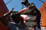 Pekerja menurunkan beras bantuan dari truk untuk dibagikan kepada warga terdampak Pemberlakuan Pembatasan Kegiatan Masyarakat (PPKM) 2021 di Kabupaten Madiun, Jawa Timur, Selasa (27/7/2021). Pemkab Madiun mulai menyalurkan bantuan beras dari pemerintah pusat total sebanyak 683,2 ton bagi 68.320 keluarga penerima manfaat masing-masing 10 kilogram guna meringankan beban selama pelaksanaan PPKM akibat pandemi COVID-19. Antara Jatim/Siswowidodo/zk