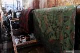 Pekerja melakukan pewarnaan pada kain batik di sebuah industri rumahan di Kampoeng Batik Jetis, Sidoarjo, Jawa Timur, Selasa (27/7/2021). Pengusaha batik setempat tetap bertahan meskipun produksi menurun dengan menjual produknya melalui pasar digital dan hanya mengandalkan pasar lokal saat Pemberlakuan Pembatasan Kegiatan Masyarakat (PPKM). Antara Jatim/Umarul Faruq/zk
