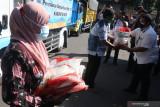 Kepala Bulog subdivre Kediri Mara Kamin Siregar (kanan) secara simbolis membagikan beras bantuan Pemberlakuan Pembatasan Kegiatan Masyarakat (PPKM) kepada Keluarga Penerima Manfaat (KPM) di Kediri, Jawa Timur, Rabu (28/7/2021). Bulog subdivre Kediri mendistribusikan beras kepada 1.394 KPM masing-masing sebanyak 10 kilogram guna mengurangi beban masyarakat saat PPKM. Antara Jatim/Prasetia Fauzani/zk