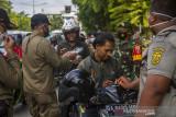 Petugas gabungan menegur warga tidak menggunakan masker saat pelaksanaan operasi yustisi Pemberlakuan Pembatasan Kegiatan Masyarakat (PPKM) level 4 di Jalan Ahmad Yani Km 6, Banjarmasin, Kalimantan Selatan, Rabu (28/7/2021). Hari pertama penegakan PPKM level 4 di Banjarmasin puluhan pengendara terjaring petugas gabungan karena melanggar protokol kesehatan yakni tidak menggunakan masker dan hanya diberikan teguran secara lisan tertulis. Foto Antaranews Kalsel/Bayu Pratama S.