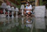 Perajin menata kerajinan kap lampu berbahan koran bekas untuk dijual di Tabanan, Bali, Kamis (29/7/2021). Sebanyak 239.469 orang pelaku usaha mikro di Bali telah menerima Bantuan Produktif Usaha Mikro (BUPM) senilai Rp287 miliar dan masing-masing memperoleh Rp1,2 juta per orang untuk meringankan perekonomian akibat pandemi COVID-19 di tahun 2021. ANTARA FOTO/Nyoman Hendra Wibowo/nym.
