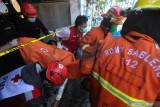 Petugas mengevakuasi jenazah korban kebakaran rumah di Perumahan Dosen Institut Teknologi Sepuluh Nopember (ITS) Surabaya, Jawa Timur, Jumat (30/7/2021). Sebanyak 12 unit kendaraan pemadam kebakaran dari Dinas Pemadam Kebakaran Kota Surabaya dikerahkan untuk memadamkan kebakaran yang menelan satu korban jiwa berinisial I (6) tersebut. Antara Jatim/Didik Suhartono/zk