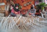 Pengrajin anyaman D'moroy, Deny Moroyati (kanan) menyelesaikan pembuatan tas dari daun pandan di Thehok, Jambi, Rabu (28/7/2021). Selama pandemi, pemilik anyaman khas Jambi yang memanfaatkan serat alam dan bahan ramah lingkungan tersebut mengaku tidak mengalami penurunan omzet karena sudah terbiasa memanfaatkan media sosial dalam memasarkan produknya yang dijual Rp150 ribu - Rp450 ribu per buah. ANTARA FOTO/Wahdi Septiawan.