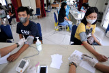 Petugas kesehatan melakukan pemeriksaan awal terhadap mahasiswa yang akan menjalani vaksinasi COVID-19 di Institut Seni Indonesia (ISI) Denpasar, Bali, Jumat (30/7/2021). Hingga Kamis (29/7) sebanyak 3.055.817 orang di Provinsi Bali telah menerima vaksin COVID-19 dosis pertama atau mencapai 101,99 persen dari target sasaran 2.996.060 orang. ANTARA FOTO/Fikri Yusuf/nym.