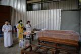 Sejumlah kerabat mendoakan jenazah korban COVID-19 sebelum dikremasi di TPU Tegal Alur, Jakarta, Jumat (30/7/2021). Pemerintah Provinsi DKI Jakarta bersama Himpunan Perkumpulan Bersatu Teguh menyediakan krematorium gratis untuk jenazah korban COVID-19 dengan kapasitas tujuh jenazah setiap harinya. ANTARA FOTO/Fauzan/nym.