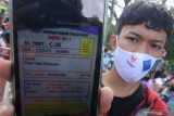 Warga memperlihatkan E-Tiket Vaksinasi sebelum mendapatkan suntikan vaksin COVID-19 di Taman Tirtoyoso, Kota Kediri, Jawa Timur, Minggu (1/8/2021). Vaksinasi massal untuk masyarakat umum di atas umur 12 tahun tersebut menerapkan tiket elektronik secara daring guna mempermudah layanan dan pembagian waktu untuk menghindari kerumunan. Antara Jatim/Prasetia Fauzani/zk