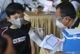 Seorang anak mendapatkan suntikan vaksin COVID-19 di Taman Tirtoyoso, Kota Kediri, Jawa Timur, Minggu (1/8/2021). Vaksinasi massal untuk masyarakat umum di atas umur 12 tahun tersebut menerapkan tiket elektronik secara daring guna mempermudah layanan dan pembagian waktu untuk menghindari kerumunan. Antara Jatim/Prasetia Fauzani/zk