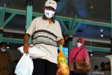 Warga membawa paket bantuan bahan pokok seusai penyerahan bantuan sosial di Pendopo Muda Graha, Kabupaten Madiun, Jawa Timur, Senin (2/8/2021). Pemkab Madiun membagikan bantuan sosial bahan pokok kepada 810 anak yatim piatu, 525 orang penyandang disabilitas, 60 orang eks penyandang psikotik dan 100 orang lanjut usia guna meringankan beban saat pandemi COVID-19. Antara Jatim/Siswowidodo/zk