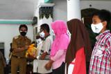 Bupati Madiun Ahmad Dawami (kiri) menyerahkan paket bantuan sosial bahan pokok kepada warga di Pendopo Muda Graha, Kabupaten Madiun, Jawa Timur, Senin (2/8/2021). Pemkab Madiun membagikan bantuan sosial bahan pokok kepada 810 anak yatim piatu, 525 orang penyandang disabilitas, 60 orang eks penyandang psikotik dan 100 orang lanjut usia guna meringankan beban saat pandemi COVID-19. Antara Jatim/Siswowidodo/zk