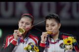 Pebulutangkis ganda Putri Indonesia Greysia Pollii (kiri) dan Apriyani Rahayu mencium medali emas yang berhasil mereka raih untuk nomor bulutangkis ganda putri Olimpiade Tokyo 2020 di Musashino Forest Sport Plaza, Tokyo, Jepang, Senin (2/8/2021). Greysia Pollii/Apriyani Rahayu berhasil meraih medal emasi setelah mengalahkan Chen/Jia Yi Fan dua set langsung. 21-19 dan 21-15. ANTARA FOTO/Sigid Kurniawan/nym.