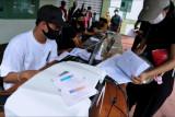 Petugas mencetak kartu sertifikat vaksinasi COVID-19 pesanan warga saat kegiatan vaksinasi COVID-19 massal di Denpasar, Bali, Selasa (3/8/2021). Jasa cetak Surat Keterangan Vaksinasi COVID-19 tersebut dijual dengan harga Rp25 ribu per buah. ANTARA FOTO/Fikri Yusuf/nym