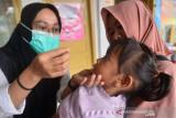 PEMBERIAN VITAMIN A ANAK DITENGAH PANDEMI COVID-19. Petugas kesehatan mengenakan masker memberikan tetesan Vitamian A kepada anak di Posyandu Kampung Keuramat, Banda Aceh, Aceh, Rabu (4/8/2021). Pemberian kapsul vitamin A secara gratis untuk anak balita usia enam sampai 59 bulan setiap bulan Februari dan Agustus di tengah pandemi COVID-19 di daerah itu tetap berjalan normal dalam upaya meningkatkan kesehatan mata  dan sistem kekebalan tubuh anak. ANTARA FOTO/Ampelsa.