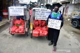 Seorang mahasiswa yang baru selesai wisuda bersama komunitas Maluku Peduli menunjukan becak berisi ratusan nasi bungkus untuk dibagikan kepada warga di Pasar Batu Merah, Kota Ambon, Provinsi Maluku, Kamis (5/8/2021). Komunitas anak muda Maluku Peduli mengumpulkan donasi untuk menyediakan 250 nasi bungkus yang dibagikan kepada warga yang membutuhkan bantuan saat Pemberlakukan Pembatasan Kegiatan Masyarakat (PPKM) di Ambon. (ANTARA FOTO/FB Anggoro)