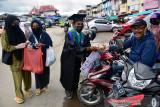Seorang mahasiswa yang baru selesai wisuda (tengah) bersama komunitas Maluku Peduli menunjukan becak berisi ratusan nasi bungkus untuk dibagikan kepada warga di Pasar Batu Merah, Kota Ambon, Provinsi Maluku, Kamis (5/8/2021).  (ANTARA FOTO/FB Anggoro)