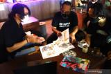 Komikus Aji Prasetyo (tengah) memperlihatkan karyanya saat berdiskusi dengan sesama anggota komunitas Malang Ilustrator Comic Artist (MICA) di Malang, Jawa Timur,  Selasa (4/8/2021). Pelaku industri kreatif setempat mengharapkan realisasi upaya pemerintah dalam mendorong terbentuknya ekosistem industri komik, animasi dan ilustrasi terutama mengenai penguatan platform digital buatan dalam negeri guna membuka peluang pasar yg lebih luas sekaligus mempermudah pelaku seni dalam memasarkan hasil karyanya. Antara Jatim/Ari Bowo Sucipto/zk