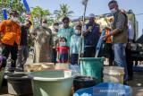 Wakil Gubernur Jawa Barat Uu Ruzhanul Ulum (kedua kanan) melihat pendistribusian air bersih untuk warga yang terdampak kekeringan di Desa Kertajaya, Garut, Jawa Barat, Rabu (11/8/2021). Wakil Gubernur Jawa Barat memberikan bantuan air bersih dan sembako kepada warga sekaligus akan segera membangun pipa dari sumber air untuk mengalirkan air kepada warga yang terdampak di sekitaran desa tersebut melalui Pemerintah Provinsi Jawa Barat. ANTARA FOTO/Novrian Arbi/agr