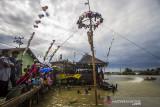 Sejumlah warga menyaksikan lomba panjat pinang di bantaran Sungai Martapura, Banjarmasin, Kalimantan Selatan, Selasa (17/8/2021). Lomba panjat pinang swadaya masyarakat tersebut dalam rangka memeriahkan HUT ke-76 Kemerdekaan Republik Indonesia. Foto Antaranews Kalsel/Bayu Pratama S.
