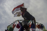 Seorang peserta mengambil hadiah saat berhasil memanjat pinang di bantaran Sungai Martapura, Banjarmasin, Kalimantan Selatan, Selasa (17/8/2021). Lomba panjat pinang swadaya masyarakat tersebut dalam rangka memeriahkan HUT ke-76 Kemerdekaan Republik Indonesia. Foto Antaranews Kalsel/Bayu Pratama S.