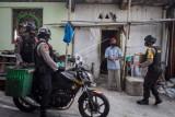 Tim Sparta Polresta Solo menyerahkan bantuan paket sembako kepada warga dengan menaiki sepeda motor yang dimodifikasi dengan