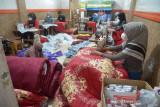 PEMASARAN PRODUK UKM SPREI SECARA ONLINE. Pekerja menggunakan masker menyelesaikan pembuatan berbagai jenis produk sprei dan sarung bantal di salah satu usaha konveksi, Banda Aceh, Aceh, Sabtu (28/8/2021). Pelaku usaha konveksi menyatakan, akibat pandemi COVID-19 terpaksa mengurangi jumlah pekerjanya hingga 50 persen dan strategi pemasaran produknya sejak setahun terakhir sudah menggunakan media sosial atau secara online dengan harga jual sprei dan sarung bantal kisaran Rp100 ribu hingga Rp800 ribu per set. ANTARA FOTO/Ampelsa.