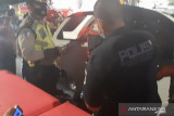Petugas Polsek Pancoran evakuasi jenazah dalam mobil