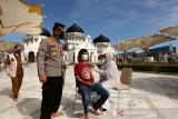 Vaksinasi Merdeka Berantas COVID. Petugas kesehatan (kanan) dan disaksikan Kapolresta Banda Aceh Kombes Pol Joko Krisdiyanto memberikan vaksin kepada warga saat vaksinasi merdeka di halaman masjid raya Baiturrahman, Banda Aceh, Aceh, Senin (6/9/2021). Vaksinasi merdeka yang digelar secara serentak pada 6-7 September 2021 di seluruh Indonesia merupakan program sinergi staf khusus Presiden bersama Kapolri dan  Panglima TNI untuk membantu pemerintah memutuskan mata rantai penyebaran serta penularan COVID-19. ANTARA/Irwansyah Putra