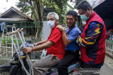Relawan Karawang Tanggap Peduli mengantar pulang penyandang disabilitas usai menerima suntikan vaksin COVID-19 di Kampung Duren, Klari, Karawang, Jawa Barat, Rabu (8/9/2021). Pemerintah Provinsi Jawa Barat mencatat per 22 Agustus 2021 sebanyak 6.000 penyandang disabilitas sudah mendapatkan vaksin COVID-19 dan menargetkan sasaran vaksinasi COVID-19 untuk penyandang disabilitas mencapai 121.648 orang. ANTARA FOTO/M Ibnu Chazar/agr