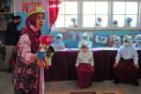 Anggota komunitas Kampung Dongeng Indonesia mendongeng di hadapan murid kelas 1 SDN 28 Kota Jambi saat kegiatan imunisasi campak di Jambi, Kamis (9/9/2021). Pemberian materi dongeng tentang manfaat imunisasi bagi anak menggunakan cara menghibur dan bahasa sederhana tersebut bertujuan menciptakan suasana bersahabat sebelum dan pada saat imunisasi dilakukan. ANTARA FOTO/Wahdi Septiawan/wsj.