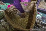 Perajin menyelesaikan pesanan kerajinan tas berbahan baku eceng gondok di Mujisela Craft, Kecamatan Labuanamas Selatan, Kabupaten Hulu Sungai Tengah, Kalimantan Selatan, Senin (13/9/2021). Menurut pemilik Mujisela Craft, permintaan berbagai jenis kerajinan tangan berbahan baku eceng gondok dan kulit jagung mengalami peningkatan hingga 90 persen di tengah pandemi COVID-19 untuk dikirim ke berbagai daerah seperti ke Jawa, Medan dan Bali yang dijual Rp10.000 sampai Rp400.000. Foto Antaranews Kalsel/Bayu Pratama S.