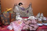 Perajin menunjukkan hasil kerajinan kain ecoprint di industri rumahan kawasan Kampung batik Jetis, Sidoarjo, Jawa Timur, Selasa (14/9/2021). Kerajinan kain ecoprint berbasis pewarna alam yang dibuat menjadi tas, pakaian, sepatu, dan kerudung tersebut dipasarkan secara daring dengan kisaran harga Rp100.000 hingga Rp600.000 tergantung model dan tingkat kesulitan. Antara Jatim/Umarul Faruq/zk