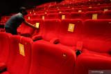 Pekerja memasang tanda silang di tempat duduk pengunjung bioskop XXI di Grand City Mall Surabaya, Jawa Timur, Selasa (14/9/2021). Pemerintah memberikan kelonggaran dengan diperbolehkannya bioskop buka kembali di wilayah-wilayah dengan status pemberlakuan pembatasan kegiatan masyarakat (PPKM) level 3 dan 2 dengan kapasitas pengunjung 50 persen, penggunaan aplikasi PeduliLindungi, telah tervaksinasi COVID-19 dosis kesatu serta kedua dan menerapkan protokol kesehatan secara ketat. Antara Jatim/Didik Suhartono/zk