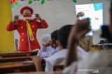 Seorang anggota Komunitas Badut Necis mencontohkan penggunaan masker yang tepat saat sosialisasi protokol kesehatan pada pembelajaran tatap muka SD Pasir Kaliki Mandiri 2 Cimahi Utara, Cimahi, Jawa Barat, Selasa (14/9/2021). Komunitas Badut Necis melakukan aksi kampanye edukasi protokol kesehatan dengan menyanyikan lagu 3M, dan membagikan masker guna mencegah penyebaran COVID-19 di lingkungan sekolah saat pembelajaran tatap muka. ANTARA FOTO/Raisan Al Farisi/agr