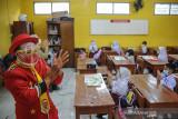 Seorang anggota Komunitas Badut Necis menyanyikan lagu 3M saat sosialisasi protokol kesehatan pada pembelajaran tatap muka SD Pasir Kaliki Mandiri 2 Cimahi Utara, Cimahi, Jawa Barat, Selasa (14/9/2021). Komunitas Badut Necis melakukan aksi kampanye edukasi protokol kesehatan dengan menyanyikan lagu 3M, dan membagikan masker guna mencegah penyebaran COVID-19 di lingkungan sekolah saat pembelajaran tatap muka. ANTARA FOTO/Raisan Al Farisi/agr