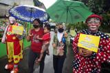 Dua badut menjemput dan mengantar warga untuk mengikuti vaksinasi COVID-19 di Pinang, Tangerang, Banten, Selasa (14/9/2021). Aksi yang dilakukan Taman Baca Badut Syariah itu dilakukan untuk mengajak warga mengikuti vaksinasi COVID-19 guna meningkatkan herd imunity atau kekebalan kelompok. ANTARA FOTO/Muhammad Iqbal/nym.