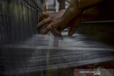 Perajin menenun benang sutra di Kampung Karanganyar Desa Cipondok, Kabupaten Tasikmalaya, Jawa barat, Rabu (15/9/2021). Kelompok Usaha Tenun Sutera Alam Mardian Putera merupakan mitra binaan Pertamina Geothermal Energy (PGE) Area Karaha dengan membudidayakan ulat sutera untuk kebutuhan bahan baku benang tenun sutera. ANTARA FOTO/Adeng Bustomi/agr