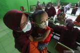 Sejumlah ibu bersama anaknya antre untuk mendapatkan layanan imunisasi di kantor Kelurahan Pesantren, Kota Kediri, Jawa Timur, Rabu (15/9/2021). Pemberian imunisasi yang seharusnya dilaksanakan di puskesmas tersebut dialihkan ke kantor kelurahan setempat untuk mengurangi interaksi sosial dan memisahkan anak dari orang sakit guna menghindari penyebaran COVID-19. Antara Jatim/Prasetia Fauzani/zk